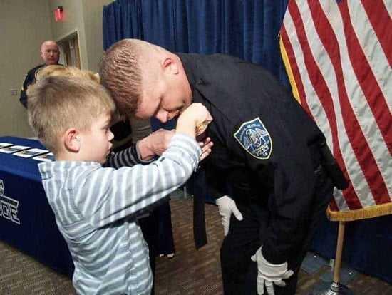 Zdjęcie policjanta przytulającego porzucone dziecko rozprzestrzeniło się po sieci lotem błyskawicy. Przypatrz się bliżej, a zrozumiesz czemu